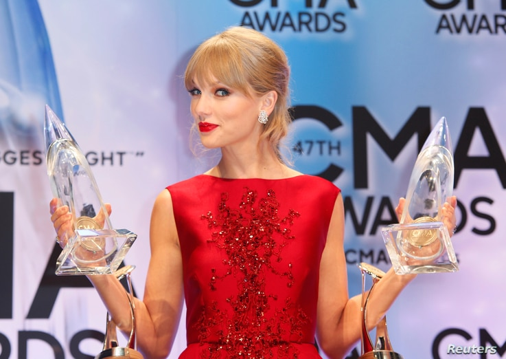 """Taylor Swift poses with her CMA Pinnacle award as well as awards for Musical Event of the Year and for Music Video of the Year, both of the latter for """"Highway Don't Care,"""" with Tim McGraw and Keith Urban, at the 47th Country Music Association Awards..."""