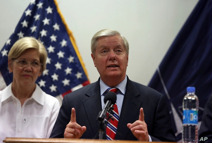U.S. Senator Lindsey Graham right, speaks during a press conference at the Resolute Support headquarters in Kabul, Afghanistan, July 4, 2017.  Senator Elizabeth Warren is shown at left.