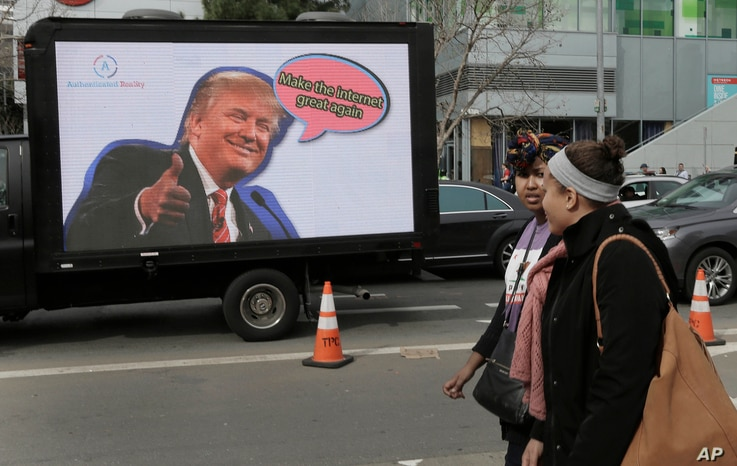 FILE - Protesting tech workers walk past a mobile billboard of Donald Trump in San Francisco, California, Feb. 13, 2017.