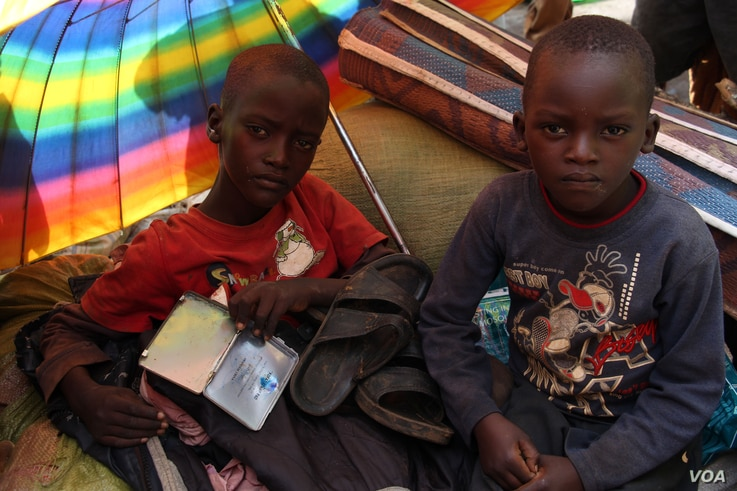 Children shield themselves from the morning sun at a reception camp in Eastern Rwanda, while they wait to be sent to one of the refugee camps set by the Rwandan government. (Mohammed Yusuf for VOA)