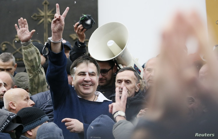 Georgian former President Mikheil Saakashvili flashes a victory sign after he was freed by his supporters in Kiev, Ukraine, Dec. 5, 2017.