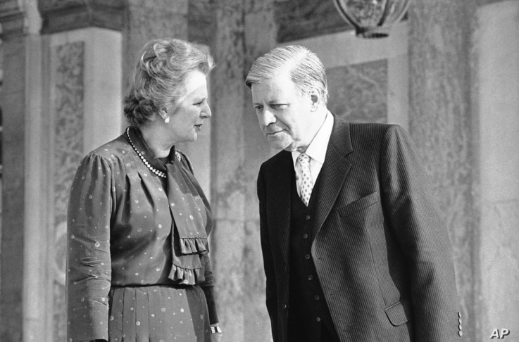 FILE - Britain's Prime Minister Margaret Thatcher, right, speaks to West German Chancellor Helmut Schmidt as they walk in the gardens of the palace of Versailles near Paris, France, after bilateral talks, June 5, 1982. Schmidt died Nov. 10, 2015, at ...