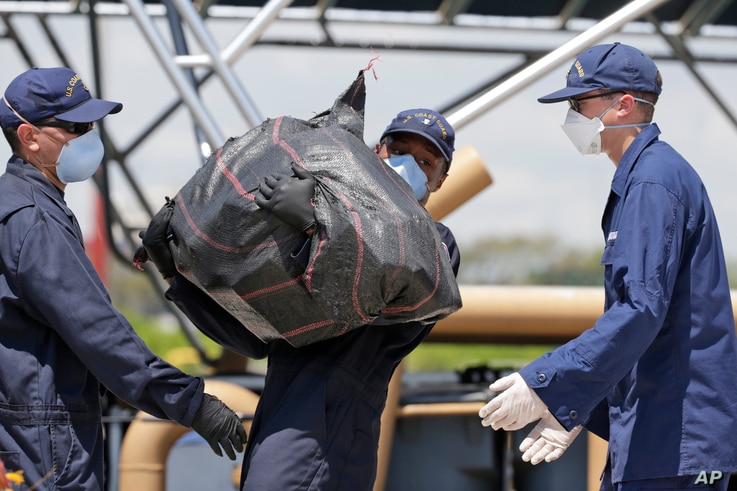 FILE - Members of the U.S. Coast Guard offload bails of over eight tons of cocaine interdicted in international waters, from the Cutter Bernard C. Webber at Coast Guard Station Miami Beach, June 13, 2016, in Miami Beach, Fla. The drugs were collected...