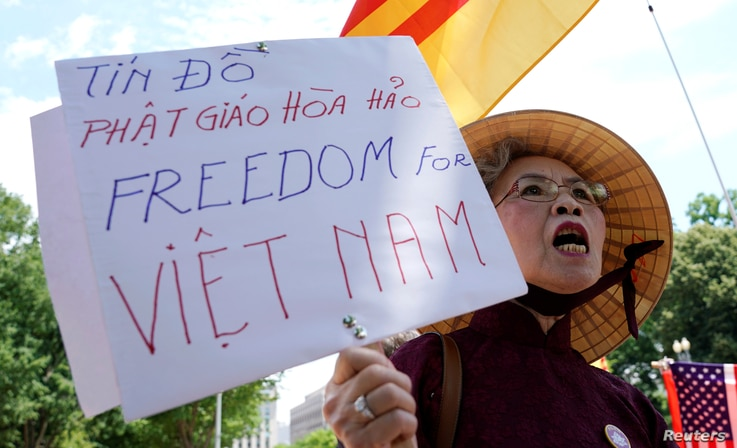 A Vietnamese-American woman protests outside the White House before President Donald Trump's meeting with Vietnamese Prime Minister Nguyen Xuan Phuc at the White House in Washington, May 31, 2017.