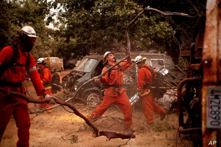Inmate firefighters clear brush to create a fire break while battling the Ferguson Fire in unincorporated Mariposa County, Calif, on Monday, July 16, 2018.