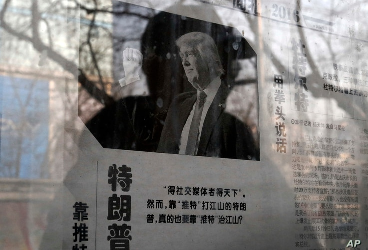 """FILE - A man reading a newspaper posted on a public newspaper bulletin board is reflected on a glass as a photo of U.S. President-elect Donald Trump is published on a Chinese newspaper with an article that reads """"Trump uses fist to talk"""" in Beijing, ..."""