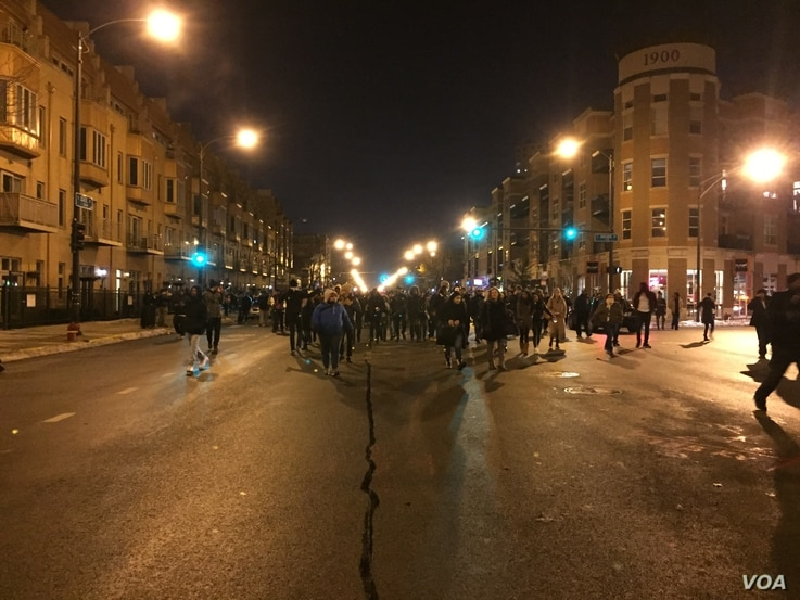 Several hundred people protesting on the streets of Chicago over a police video showing a white officer shooting a black teenager 16 times. (C. Presutti/VOA)