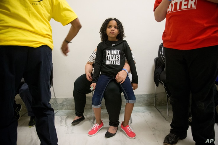Mari Copeny, 8, of Flint, Mich. sits on the lap of her mother, Lulu Brezzell as they and other Flint residents and supporters wait outside the room where Michigan Gov. Rick Snyder and EPA Administrator Gina McCarthy testify before a House Oversight a...