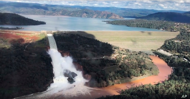 This image from video provided by the office of Assemblyman Brian Dahle shows water flowing over an emergency spillway of the Oroville Dam in Oroville, Calif., Feb. 10, 2017.
