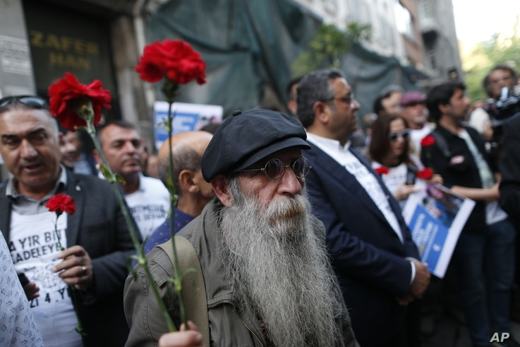 FILE - A demonstrator holds carnations during a protest to mark the anniversary of the nationwide summer 2013 Gezi Park protests, in Istanbul, May 31, 2017. Protests began in 2013 as a small environmental sit-in against government plans to raise a ce...