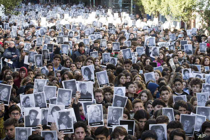 People hold up pictures of the victims of the 1994 bombing of the AMIA Jewish community center on the 21st anniversary of the terror attack in Buenos Aires, Argentina, July 17, 2015.