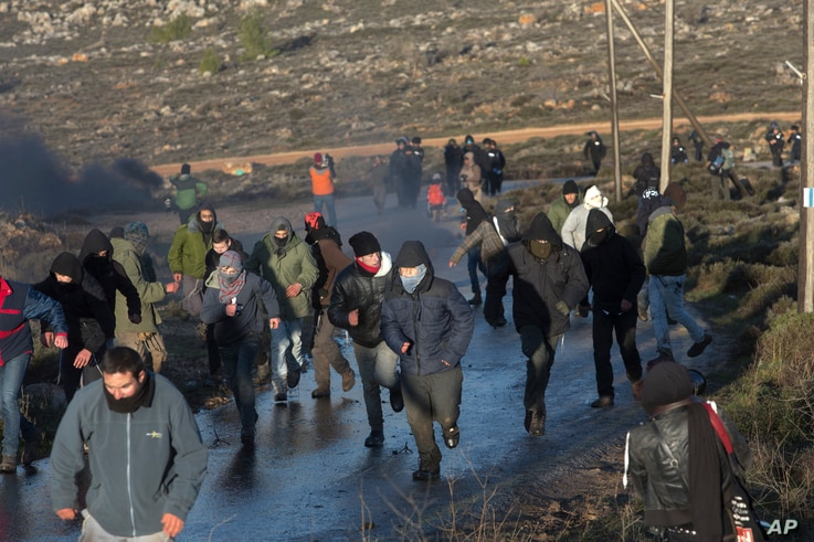 Jewish settlers run from police outside the Amona outpost in the West Bank, Feb. 1, 2017. The military issued eviction orders the day before, telling residents to evacuate Amona within 48 hours and blocked roads leading to the outpost.