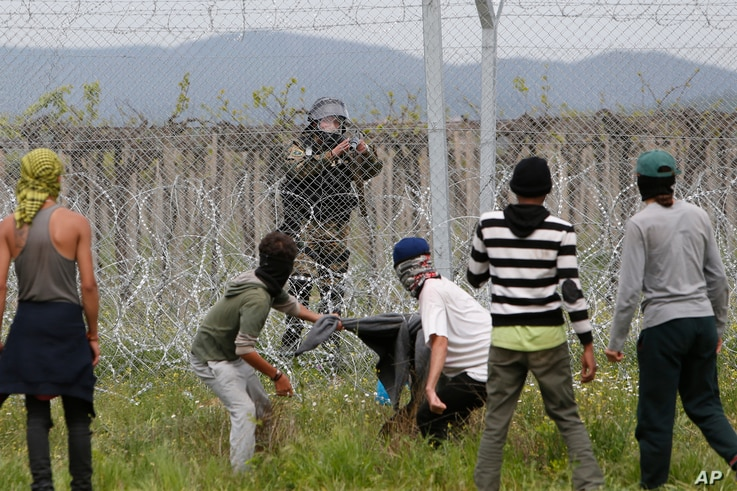 Migrant men trying to remove barbed wire along the fence clash with Macedonian police at the northern Greek border point of Idomeni, Greece, April 13, 2016.
