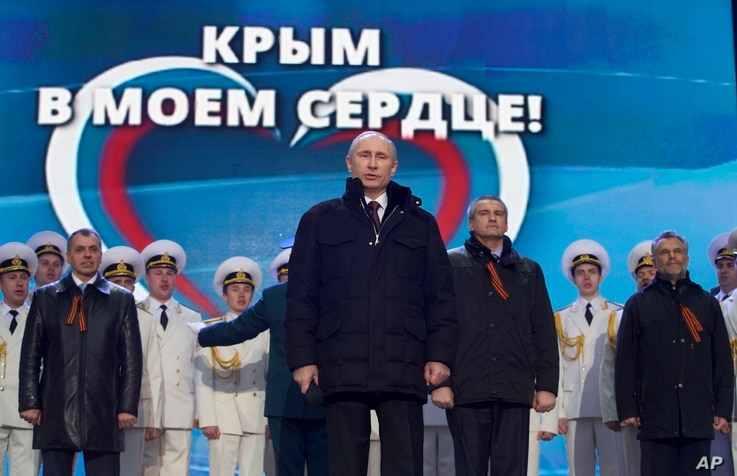 """Russian President Vladimir Putin, with leaders of newly-annexed Crimea in the background, is seen at a rally in Moscow, March 18, 2014. The sign in the back reads """"Crimea is in my heart!"""""""