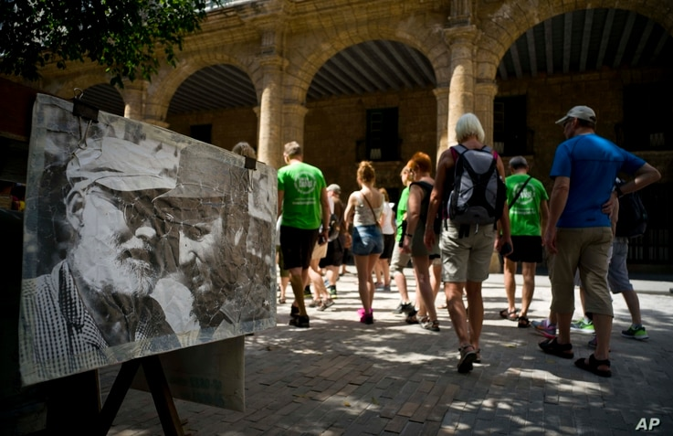 Tourists walk next to an weathered old photo of Ernest Hemingway and Fidel Castro in Havana, Cuba, March 14, 2016. U.S. President Barack Obama will travel to Cuba on March 20.
