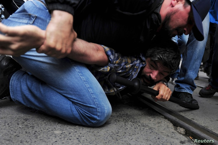 FILE - A plainclothes police officer detains a demonstrator during a protest in central Istanbul, May 31, 2014. Protesters were marking the one-year anniversary of major anti-government demonstrations.