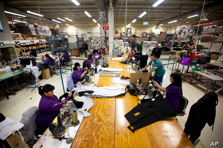Workers manufacture car dash mats at a maquiladora belonging to the TECMA group in Ciudad Juarez, Mexico, Dec. 27, 2013. With the implementation of NAFTA, many North American and international companies moved manufacturing to Mexico at a lower cost. ...