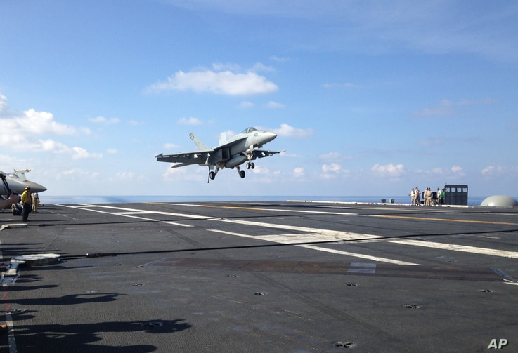 An FA-18 jet fighter takes off on the USS John C. Stennis aircraft carrier in the South China Sea on April 15, 2016.