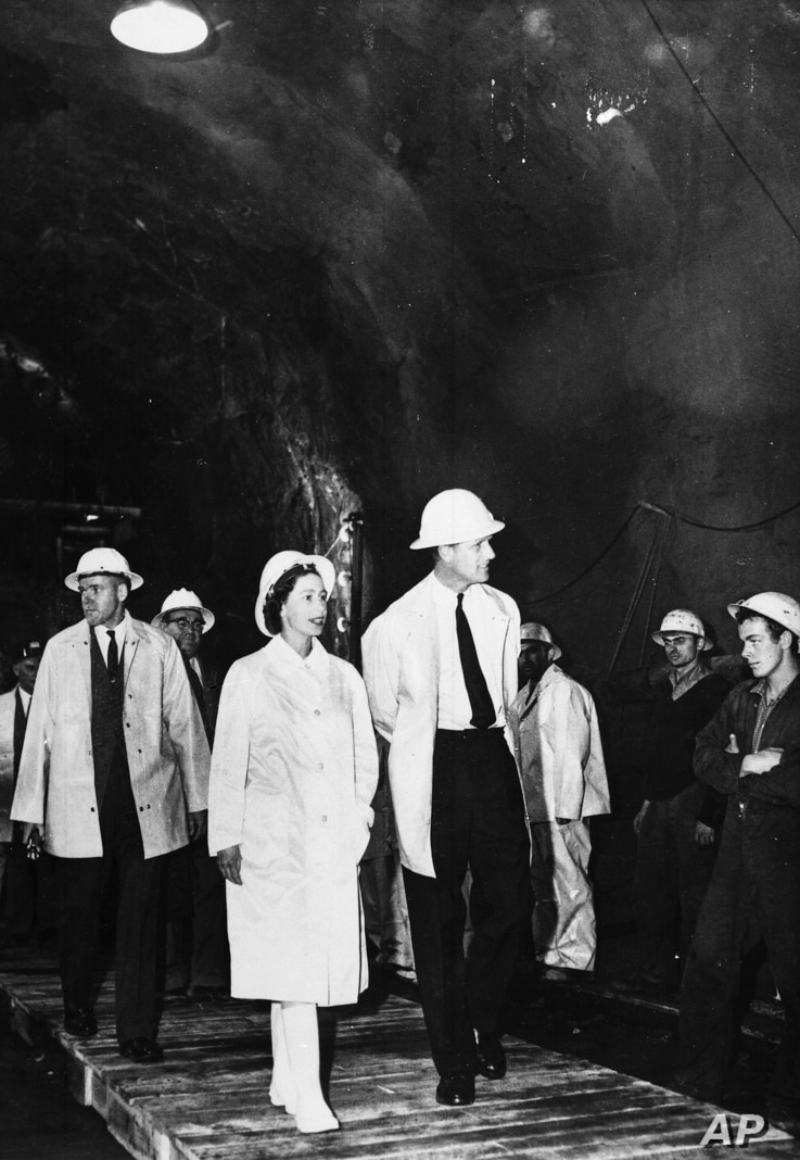 FILE - Queen Elizabeth II and her husband, Prince Philip, walk through the Gieehi Dam tunnel, part of a $320 million hydroelectric and irrigation scheme, inspecting work on the Snowy Mountain project at Cabrumurra, New South Wales, March 9, 1963.