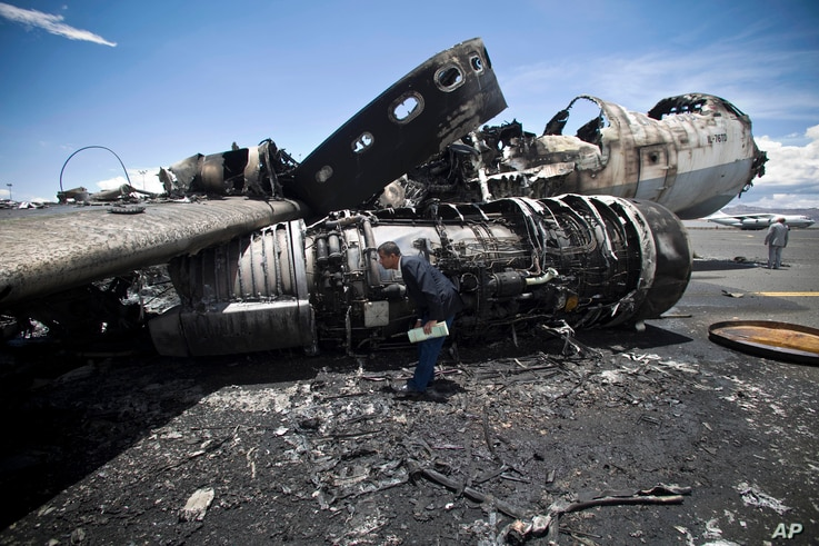 An airport official looks at the wreckage of a military transport aircraft destroyed by Saudi-led airstrikes, at the Sanaa International airport, in Yemen, May 5, 2015.