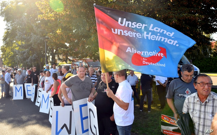 """FILE - Supporters of the Alternative for Germany party hold posters reading """"Merkel must go"""" and a flag reading """"Our country, our homeland,"""" as they protest during a campaign event of German Chancellor Angela Merkel in Bitterfeld, eastern Germany, Au..."""