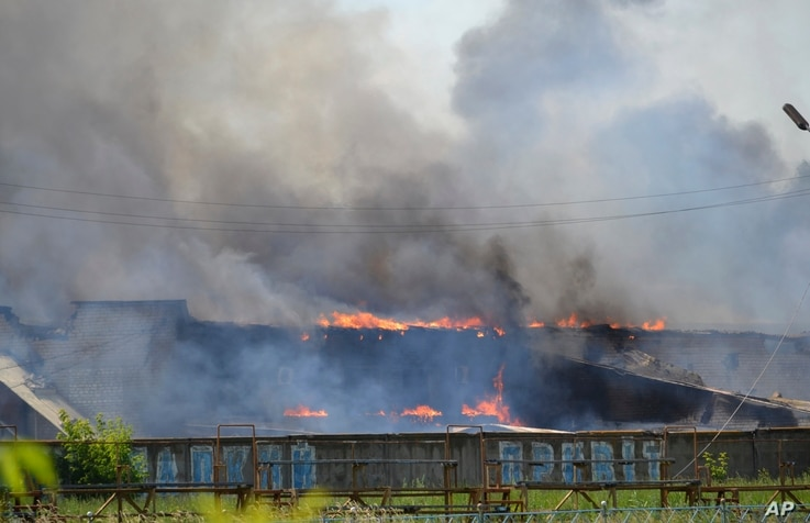 Smoke rises from the burning furniture factory after a mortar attack by Ukrainian government troops in Slovyansk, eastern Ukraine, June 8, 2014.