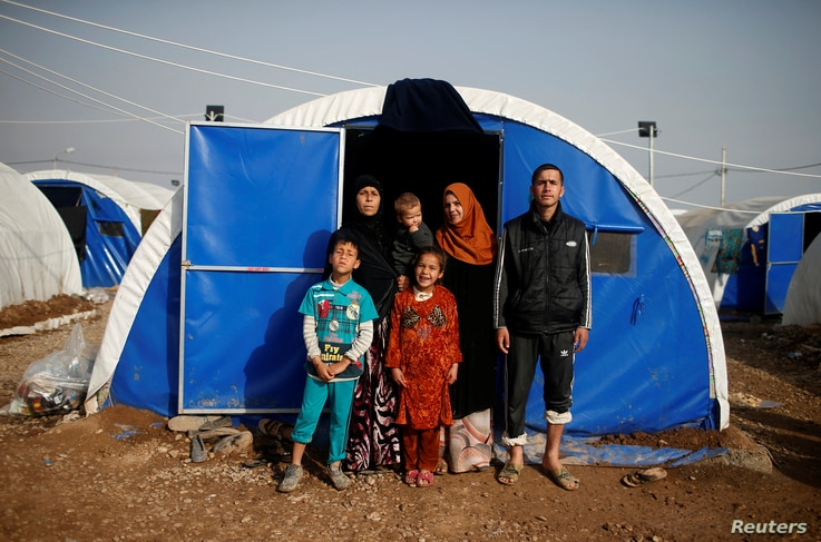 Displaced Iraqi Gorha Mahmoud (L), 40, poses for a photograph with family at Hammam al-Alil camp south of Mosul, Iraq, March 29, 2017.