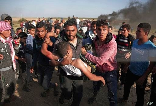 Palestinian protesters carry a wounded man who was shot by Israeli troops during a protest near the Gaza Strip border with Israel, in eastern Gaza City, March 31, 2018.