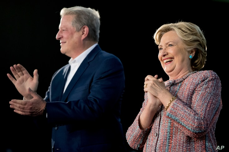 Democratic presidential candidate Hillary Clinton, accompanied by former Vice President Al Gore, takes the stage for a rally at Miami Dade College in Miami, Fla., Oct. 11, 2016.