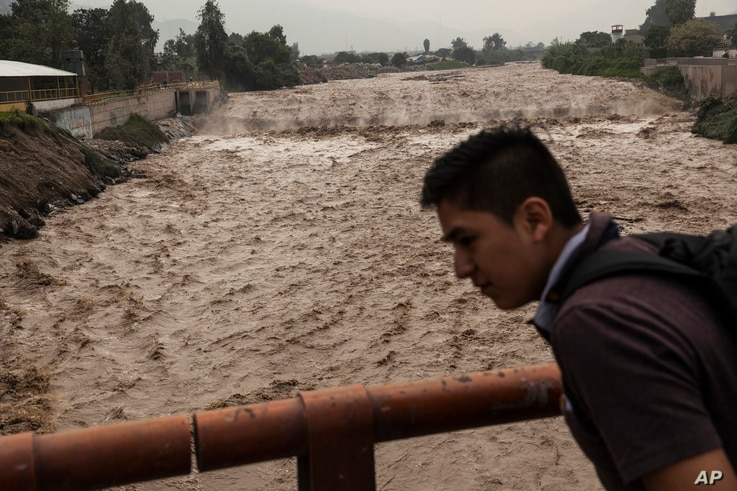 A man looks at the flow of the Huaycoloro river in Lima, Peru, March 16, 2017.