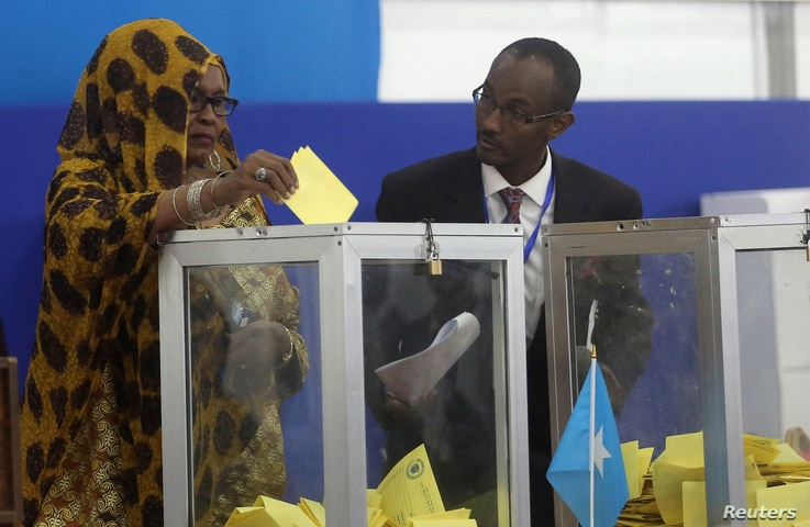 FILE - A Somali lawmaker casts her ballot during the presidential vote at the airport in Somalia's capital Mogadishu, Feb. 8, 2017.