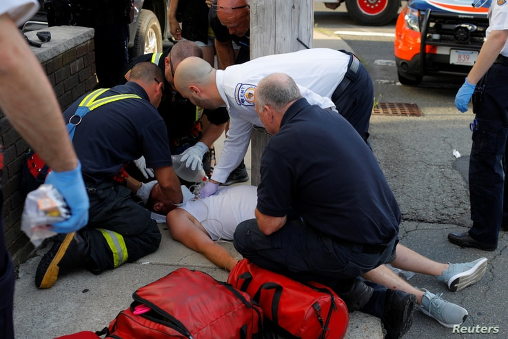 FILE - Paramedics and firefighters treat a man who was found unresponsive on a sidewalk after overdosing on opioids in Everett, Massachusetts, August 23, 2017.