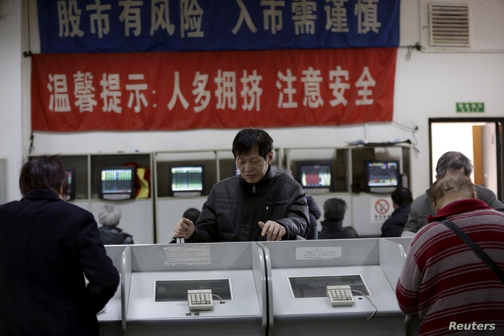 Investors look at computer screens showing stock information on the first trading day after the week-long Lunar New Year holiday at a brokerage house in Shanghai, China, Feb. 15, 2016.