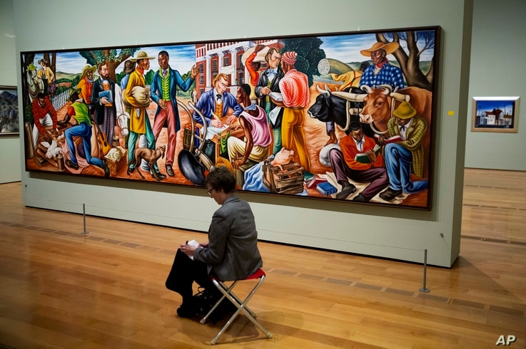 "Hale Woodruff's 1942 painting ""Opening Day at Talladega College,"" is displayed as a docent takes notes during a tour of the exhibit ""Cross Country: The Power of Place in American Art, 1915-1950,"" at the High Museum of Art in Atlanta, Feb. 6, 2017."