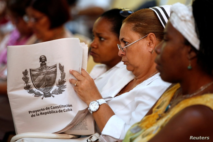 A Cuban nurse holds the draft proposal of changes to the constitution during the beginning of a public political discussion to revamp a Cold War-era constitution at the Nguyen Van Troi Polyclinic in Havana, Aug. 13, 2018.