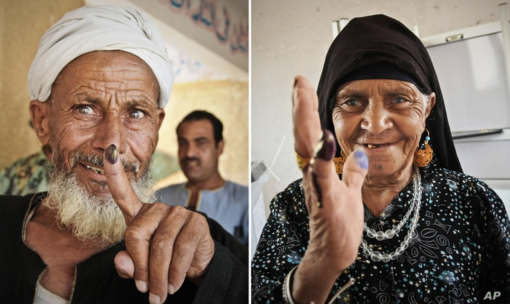 Egyptians show their inked fingers after casting their votes in Giza, Egypt.