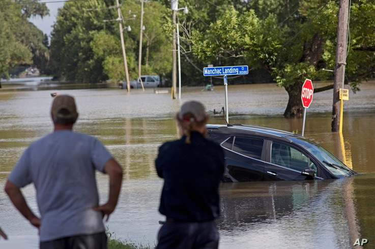 Residents survey the flood water on Old Jefferson Highway at Bayou Manchac in Prairieville, La., Tuesday, Aug. 16, 2016.