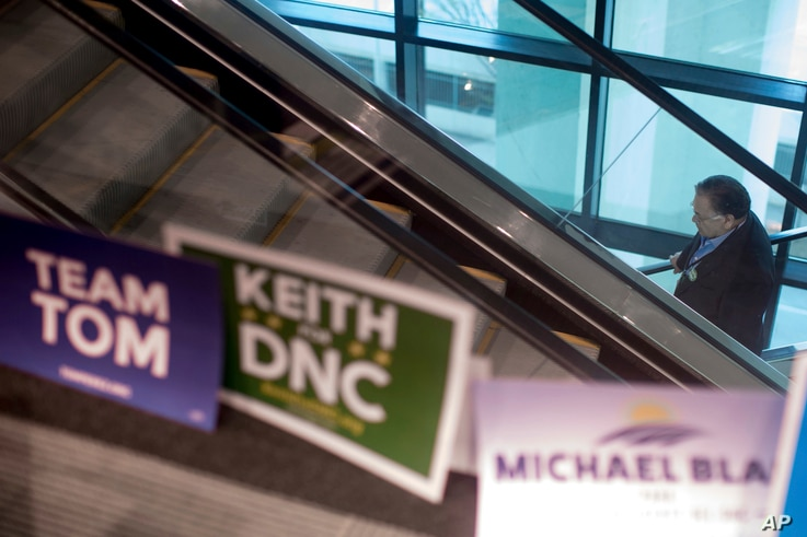 A man rides an escalator as campaign signs are seen before the general session of the Democratic National Committee winter meeting in Atlanta, Georgia, Feb. 25, 2017.