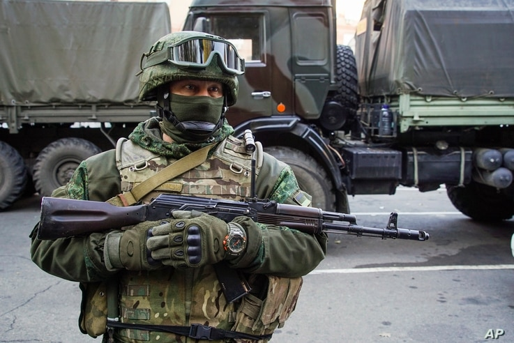 FILE - A pro-Russia rebel stands guard during preparations for a prisoner exchange in Donetsk, eastern Ukraine, Oct. 29, 2015.