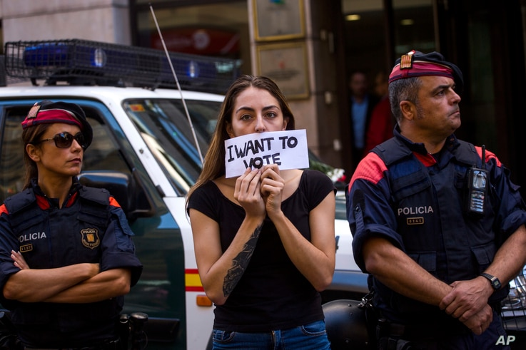 A woman protests holding a sign next to Mossos d'Esquadra police officers, in Barcelona, Spain, Sept. 20, 2017.