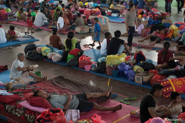 Villagers rest at a temporary evacuation center for people living near Mount Agung, a volcano on the highest alert level, inside a sports arena in Klungkung, on the resort island of Bali, Indonesia, Sept. 28, 2017, in this photo taken by Antara Foto....