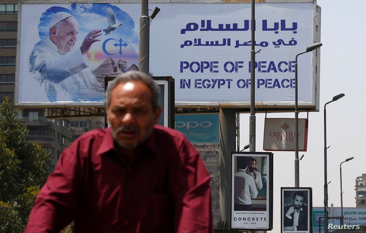A man rides a bicycle past a billboard ahead of Pope Francis' visit in Cairo, Egypt, April 26, 2017.