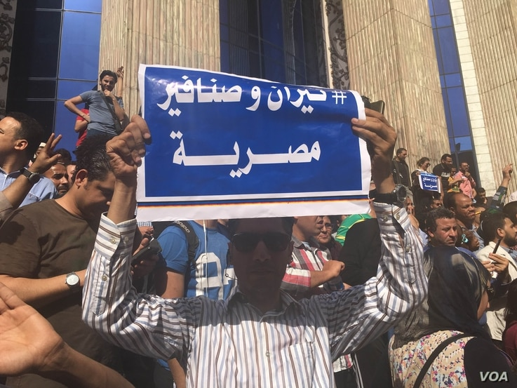"""An Egyptian protester holds a sign saying in Arabic """"Tiran and Sanafir are Egyptian,"""" referring to Red Sea islands Egypt plans to cede control of to Saudi Arabia in downtown Cairo, April 15, 2016. (VOA/ H. Elrasam)"""