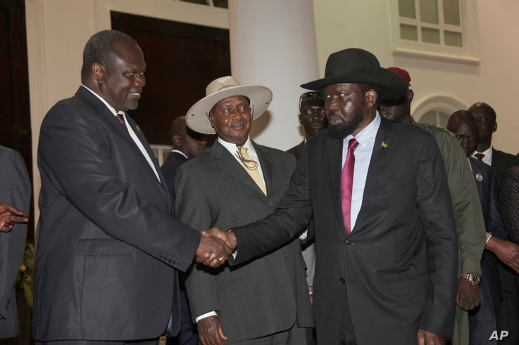 In this July 7, 2018 photo, former Vice President of South Sudan Riek Machar, left, greets South Sudan President Salva Kiir as Uganda President Yoweri Museveni, center, looks on as they meet for a security meeting to find a lasting solution to insecu...