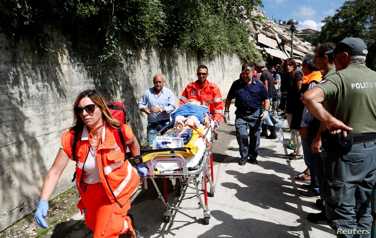 An injured person is carried away on a stretcher following an earthquake at Pescara del Tronto, central Italy, Aug. 24, 2016.