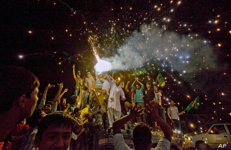 Supporters of Pakistan Muslim League-N party release fireworks to celebrate their party victory in the parliamentary election at outside the party's headquarter in Lahore, May 12, 2013.