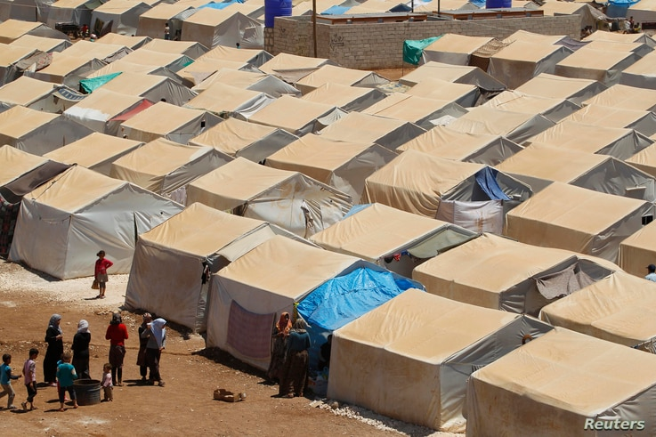 Women talk and children play around the tents of the Bab Al-Nour internally displaced persons (IDP) camp, north of Aleppo, beside the Syrian-Turkish border, May 18, 2014.