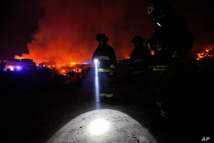 A firefighter shines a flashlight as he stands with others near burning homes as a forest fire rages towards urban areas in the city of Valparaiso, Chile, Sunday April 13, 2014.