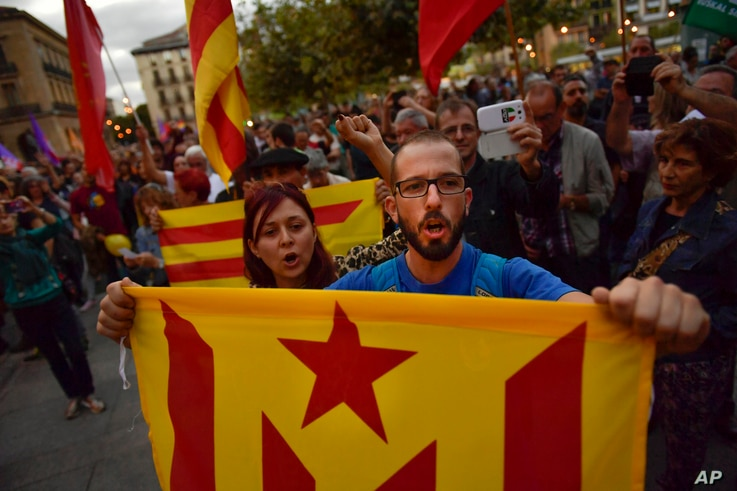 """Pro-independence supporters hold up """"esteleda"""" or pro-independence flags and shout slogans as they walk along the street during a demonstration in Pamplona, Spain, Oct. 3, 2017, protesting against the use of force by police."""