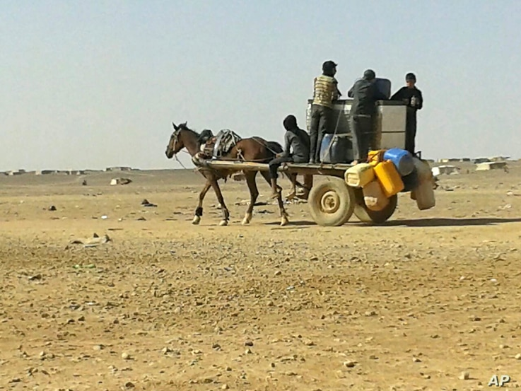 FILE - Syrian refugees ride a donkey cart full of water bottles at the Ruqban border camp, June 25, 2016.